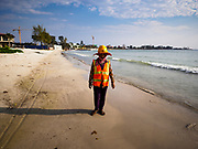 """12 FEBRUARY 2019 - SIHANOUKVILLE, CAMBODIA: A Cambodian construction worker walks down the beach near the Blue Bay resort development after work. Blue Bay is a Chinese casino and resort being built in Sihanoukville. There are about 50 Chinese casinos and resort hotels either open or under construction in Sihanoukville. The casinos are changing the city, once a sleepy port on Southeast Asia's """"backpacker trail"""" into a booming city. The change is coming with a cost though. Many Cambodian residents of Sihanoukville  have lost their homes to make way for the casinos and the jobs are going to Chinese workers, brought in to build casinos and work in the casinos.       PHOTO BY JACK KURTZ"""