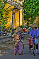 Two women wearing traditional conical hats and riding bicycles stop for a chat in Hoi An's old town.