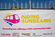 The Riding Sunbeams banner next to array of solar panels next to the line near Aldershot Railway Station on 23rd August 2019 in Aldershot, United Kingdom. This innovative project is the first in the UK to power the railway with electricity generated from solar power and, if successful, could see many Network Rail sites across the country adapting this sustainable energy approach. Riding Sunbeams is a social enterprise, run by 10:10 Climate Action. Built with Community Energy South and partnered with Network Rail and The Department for Transport and by InnovateUK.  Aldershot, Hampshire, United Kingdom. Riding Sunbeams is a world leading project to connect solar panels directly into electrified rail routes to power the trains. Direct supply of solar power to rail traction systems has never been done. But it has huge potential - from metros, trams and railways in the UK and around the world.