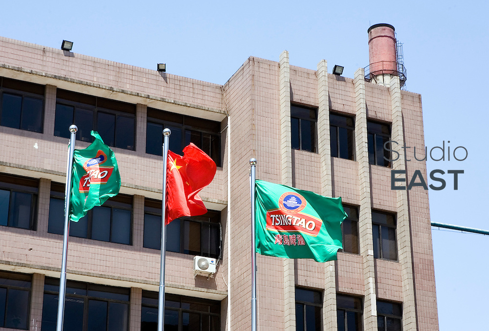 SHANDONG PROVINCE, CHINA - May 17: The Chinese and the Tsingtao beer flag outside Tsingtao brewery in Tsingtao beer street on May 17, 2009 in the town of Qingdao, Shandong province, China. Tsingtao beer is the most famous beer in China. Produced in the city of Qingdao in a brewery originally founded by Germans in 1903, the beer has now its street: Dengzhou Road, nicknamed 'beer street', just in the shadow of the brewery.  The street is home to over 60 bars and beer shops, where tourists and locals enjoy daily fresh beer just made out of the brewery, along with a variety of seafood. (Photo by Lucas Schifres/Getty Images)