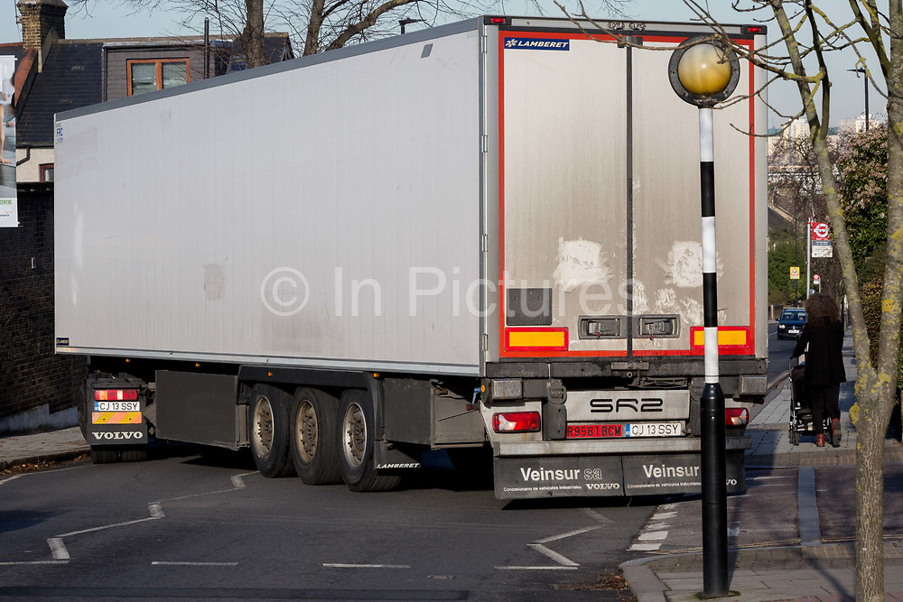 A Romanian-registered HGV lorry attempts to make a turn from Ferndene Road onto Herne Hill SE24, on 10th February 2019, in London, England. Large lorries regularly become stuck here while making this turn while following their SatNavs across south London roads.