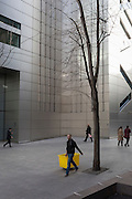 A contractor with a yellow bin passes through a landscape of corporate office space of modern architecture, on 16th February 2017, in the City of London, England.