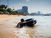 06 JANUARY 2015 - PATTAYA, CHONBURI, THAILAND:  A Thai boy swims in an inner tube on Pattaya beach. The Thai government has announced plans to clean up Pattaya beach, one of the most famous beaches in Thailand. Pattaya is about 2.5 hours from Bangkok. They plan to reduce the number of umbrella and chaise lounge vendors on the beach and regulate the personal watercraft and parasailing vendors on the beach. The government has already cleaned up beaches on Phuket island and Hua Hin.   PHOTO BY JACK KURTZ