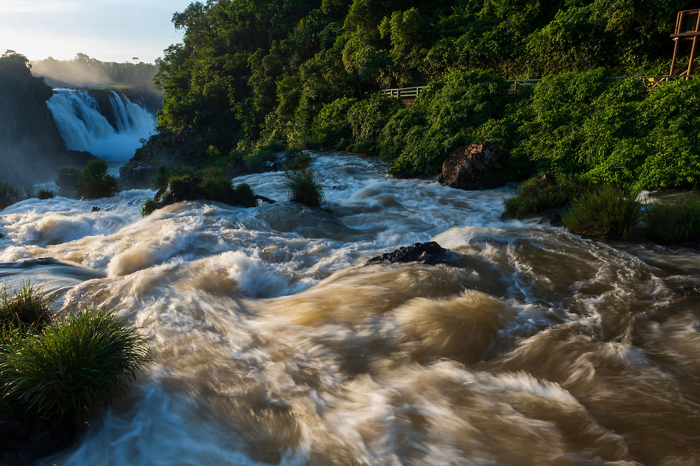 Iguazu Falls, Brazil - March 27, 2019: Rushing water at Iguazu Falls, viewed from a platform near the Devil's Throat section on the Brazilian side of the waterfall.