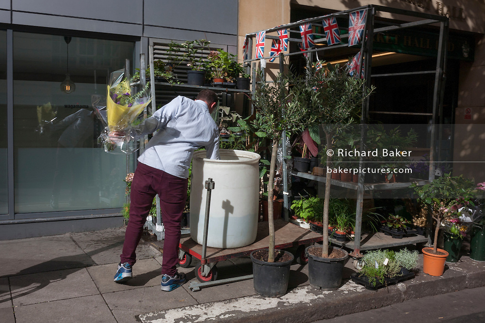 Surrounded by his racks of plants, a Covent Garden florist leans into a water butt while holding a bouquet of flowers.
