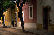 Man and children walking in a colourful street in Stone Town, the colonial part of Ilha de Mozambique