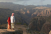 Local man and child looking at mountainous landscape at Dixsam with a view to the Hagier Mountains.  Socotra, Yemen