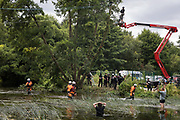 Police officers from Hampshire Police Marine Support Unit move environmental activists from HS2 Rebellion away from an ancient alder tree which they had been trying to protect from destruction during works for the HS2 high-speed rail link on 24th July 2020 in Denham, United Kingdom. A large security operation involving officers from the Metropolitan Police, Thames Valley Police, City of London Police and Hampshire Police as well as the National Eviction Team ensured the removal of the tree by HS2 despite the protests by activists.