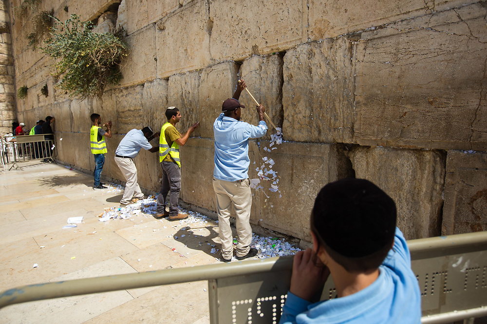A Jewish child observes, while workers remove notes containing prayers and messages which were left by visitors, from the cracks between the stones of the Western Wall, Judaism's holiest prayer site, in the Old City of Jerusalem, Israel, on September 17, 2017. The clean-up which takes place ahead of the upcoming Jewish New Year Holiday, clears the wall's crevices and frees up space for more notes that people of all faiths slip between its stones, believing that requests deposited at the site are more likely to be heard by God.