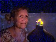 Selfie by Ann Parry by oil lamp, in backyard