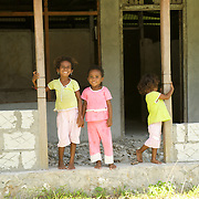 Papuan kids at the entry of a house.