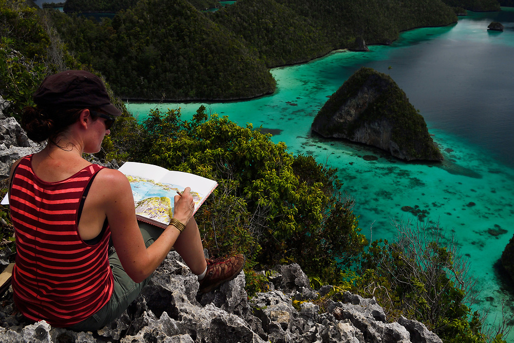 """Artist Stéphanie Ledoux at work, painting Karst landscapes in Waiag archipelago, Raja Ampat, Western Papua, Indonesian controlled New Guinea, on then Science et Images """"Expedition Papua, in the footsteps of Wallace"""", by Iris Foundation"""