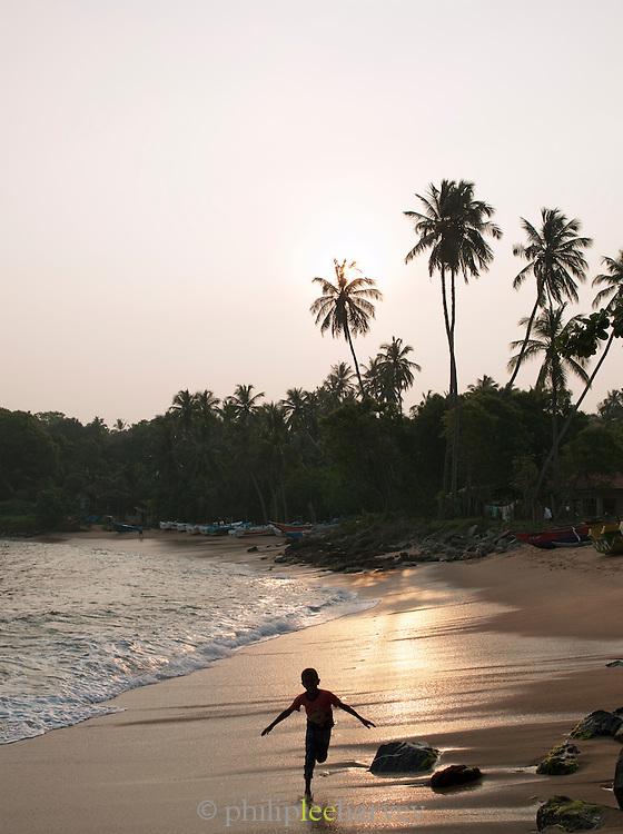 Local young boy running along a wet sandy beach at Tangalle, Sri Lanka