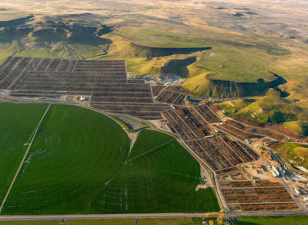 Feed lot along the Snake River just south of Boise with desert rim above and pivot irrigation below the corrals. No Property Release