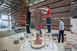 © licensed to London News Pictures. London, UK 24/06/2012. Two architects  carefully positioning cans to a ketchup bottle made of cans, when it's completed it will have nearly 2,500 cans. Teams of leading architects, designers and engineers competing today as they sculptures from cans of food at One Canada Square Shopping Centre today. Photo credit: Tolga Akmen/LNP