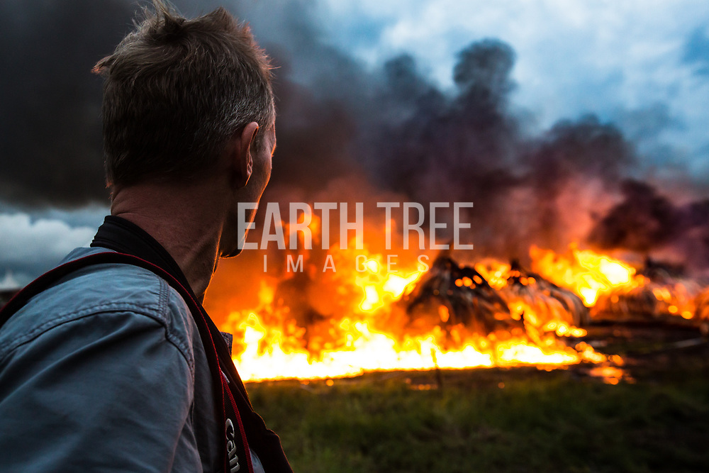 Paul Hilton watches more than 100 tonnes of Elephant and Rhino tusks burn in Kenya. The ivory represents the poaching of more than 8,000 Elephants.