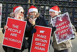 © Licensed to London News Pictures. 18/12/2019. London, UK. Pro-Brexit supporters with placards and wearing Santa hats protest outside the Houses of Parliament. Photo credit: Dinendra Haria/LNP