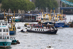 London Bridge, London, June 15th 2016. A flotilla of fishing boats led by UKIP's Nigel Farage heads through Tower Bridge in protest against the EU's Common Fisheries Policy and in support of Britain leaving the EU. PICTURED: Farage's boat, centre, makes its way through the flotilla in the Pool of London.