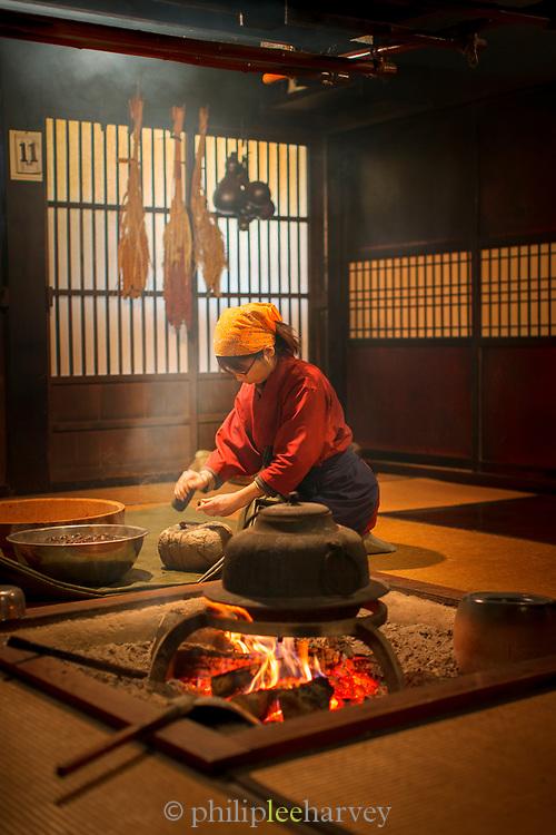 Woman cooking in traditional kitchen, Shirakawa-go, Japan