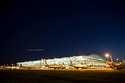 """With faint traces of an evening metor shower in the sky, a wide exterior view of Heathrow Airport's Terminal 5 building in West London. Created by the Richard Rogers Partnership (now Rogers Stirk Harbour and Partners). As the last light of the day fades and a departing aircraft's lights streak across the sky, the brightness of terminal lights shine through massive panes of window glass. At a cost of £4.3 billion, the 400m long T5 is the largest free-standing building in the UK with the capacity to serve around 30 million passengers a year. The Terminal 5 public inquiry was the longest in UK history, lasting four years from 1995 to 1999. From writer Alain de Botton's book project """"A Week at the Airport: A Heathrow Diary"""" (2009). ......"""