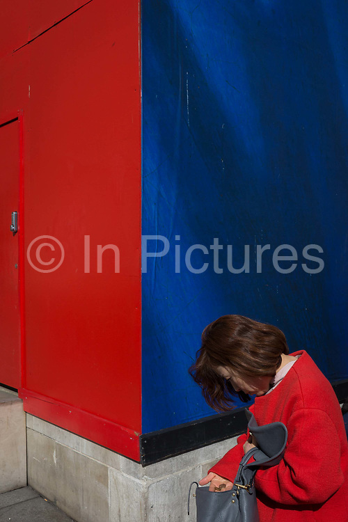 A woman wearing red searches for coins from her bag, against a background of primary colours, on 21st March 2017, outside the National Gallery, in London, England. In an era of online banking and chip and PINs, cash in ones bag is still needed for the trivial when out and about.