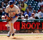 April 22, 2012; Houston, TX, USA; Los Angeles Dodgers third baseman Juan Uribe (5) bobbles a ground ball against the Houston Astros during the sixth inning at Minute Maid Park. Mandatory Credit: Thomas Campbell-US PRESSWIRE