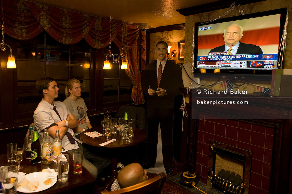 Young couple watch John McCain concede defeat by life-sized cut-out of Barack Obama after overnight 2008 election London party