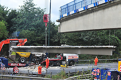© Licensed to London News Pictures. 28/08/2016<br /> M20 BRIDGE COLLAPSE,KENT.<br /> <br /> The bridge being lifted off the M20 by TWO CRANES and loaded onto a transporter lorry.<br /> <br /> The M20 is still closed today after a pedestrian bridge collapsed on to the motorway after being struck by a digger on a transporter lorry.  Emergency work to clear the scene is continuing with engineers working all night.<br /> (Byline:Grant Falvey/LNP)