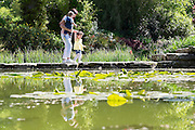 © Licensed to London News Pictures. 13/05/2015. Cliveden, UK. People cross stepping stones int he Water Garden. Visitors to the National Trust property Cliveden House enjoy the warm and sunny weather today 13th May 2015. Photo credit : Stephen Simpson/LNP