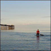 Man paddling in the sea with his dog