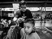 12 SEPTEMBER 2018 - BANGKOK, THAILAND: A barber gives a child a haircut at Hua Lamphong train station in Bangkok. Barber schools set up in the station and offer free haircuts to travelers.   PHOTO BY JACK KURTZ