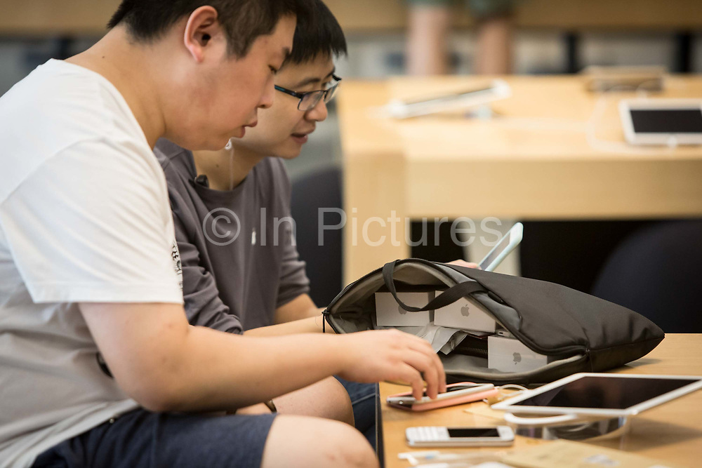 Customers try out Apple Products including Apple Inc.s iPhone 6s and iPhone 6s Plus ahead of the sales launch at the companys store at the IAPM shopping mall in Shanghai, China, on Friday, Sept. 25, 2015.