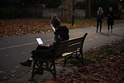 A woman works at dusk on a park bench on the first day of national lockdown on 5th of November 2020, East London, United Kingdom. The UK Govenrment introduced a 4 week lockdown from November 5th - December 2nd to combat the cororanavirus outbreak.