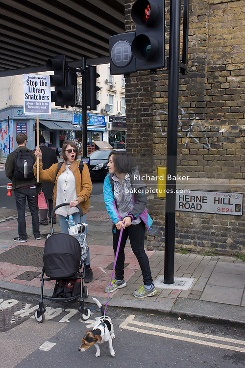 Bystanders watch campaigners against the closure by Lambeth council  of Carnegie Library in Herne Hill, south London, as they march through Brixton after emerging from the premises on the 10th day of occupation, 9th April 2016. The local community have been occupying their important resource for learning and social hub and after a long campaign, Lambeth have gone ahead and closed the library's doors for the last time because they say, cuts to their budget mean millions must be saved. They plan to re-purpose it into a gym although details are unknown.
