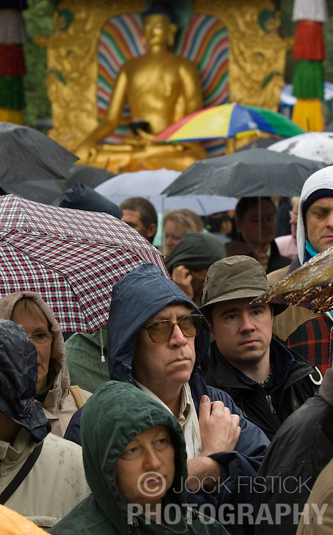 """HUY, BELGIUM - MAY-29-2006 - The faithful prepare themselves and wait in the pouring rain to see the Dalai Lama during an inauguration ceremony for a new temple at the Institute Yeunten Ling in Huy, Belgium. The new temple was named Thubten Sherab Ling by the Dalai Lama, which means """"The garden of study and practice of the teachings of the Enlightened One"""".  This marks the start of the Dalai Lama's five-day visit to Belgium where he will speak in both Brussels and Antwerp. (PHOTO © JOCK FISTICK)"""