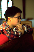 Young parishioner age 12 in a moment of reflection at church.  WesternSprings  Illinois USA