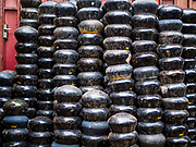 "28 MARCH 2017 - BANGKOK, THAILAND: A stack of finished monks' bowls on Soi Baan Bat in Bangkok. The bowls are made from eight separate pieces of metal said to represent the Buddha's Eightfold Path. The Monk's Bowl Village on Soi Ban Baat in Bangkok is the only surviving one of what were originally three artisan's communities established by Thai King Rama I for the purpose of handcrafting ""baat"" the ceremonial bowls used by monks as they collect their morning alms. Most monks now use cheaper factory made bowls and the old tradition is dying out. Only six or seven families on Soi Ban Baat still make the bowls by hand. Most of the bowls are now sold to tourists who find their way to hidden alleys in old Bangkok. The small family workshops are only a part of the ""Monk's Bowl Village."" It is also a thriving residential community of narrow alleyways and sidewalks. The area is also spelled Ban Bat or Baan Bat.           PHOTO BY JACK KURTZ"