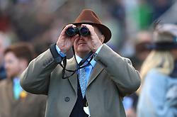 A racegoer watches the action through binoculars during St Patrick's Thursday of the 2018 Cheltenham Festival at Cheltenham Racecourse.