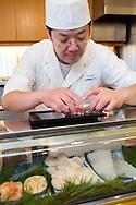 Sushi chef Masatoshi Yoshino is arranging nigiri sushi on a plate at his restaurant Yoshino Sushi Honten, Tokyo, Japan