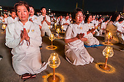 "14 FEBRUARY 2014 - KHLONG LUANG, PATHUM THANI, THAILAND: Lay people participate in the evening candle light procession for Makha Bucha Day at Wat Phra Dhammakaya. The aims of Makha Bucha Day are: not to commit any kind of sins, do only good and purify one's mind. It is a public holiday in Cambodia, Laos, Myanmar and Thailand. Many people go to the temple to perform merit-making activities on Makha Bucha Day. The day marks four important events in Buddhism, which happened nine months after the Enlightenment of the Buddha in northern India; 1,250 disciples came to see the Buddha that evening without being summoned, all of them were Arhantas, Enlightened Ones, and all were ordained by the Buddha himself. The Buddha gave those Arhantas the principles of Buddhism, called ""The ovadhapatimokha"". Those principles are:  1) To cease from all evil, 2) To do what is good, 3) To cleanse one's mind. The Buddha delivered an important sermon on that day which laid down the principles of the Buddhist teachings. In Thailand, this teaching has been dubbed the ""Heart of Buddhism."" Wat Phra Dhammakaya is the center of the Dhammakaya Movement, a Buddhist sect founded in the 1970s and led by Phra Dhammachayo.    PHOTO BY JACK KURTZ"