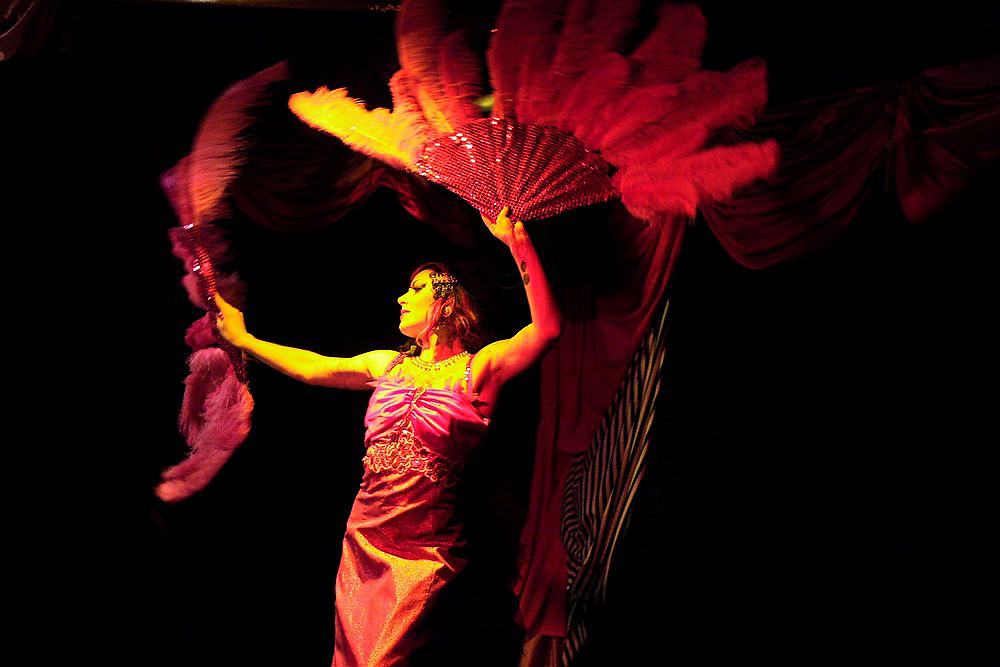 A woman dances with large feather fans at a burlesque cabaret performance at the Can Can in Seattle, Washington.