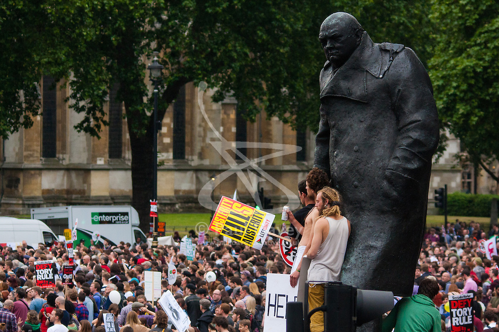 London, June 20th 2015. Thousands of people converge on the streets of London to join the People's Assembly Against Austerity's march from the Bank of England to Parliament Square. PICTURED: Winston Churchill's statue looks down on the crowd in Parliament Square.