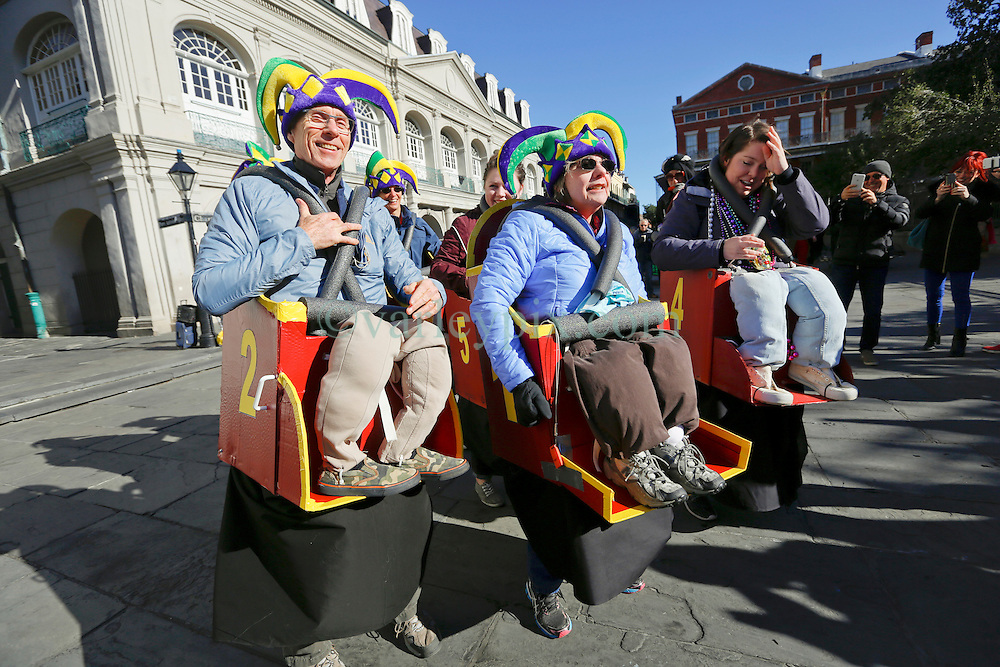 09 February 2016. New Orleans, Louisiana.<br /> Mardi Gras Day. A group dressed as a collective roller coaster go through the hilarious actions of a ride. Some of the many bright and coolurful costumes in the French Quarter. <br /> Photo©; Charlie Varley/varleypix.com