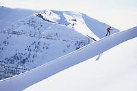 A backcountry skier climbs a snowy ridgeline in the western Teton range, Wyoming.