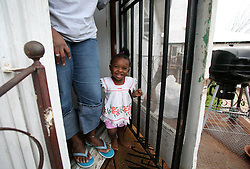 09 July 2006. New Orleans. Louisiana. <br /> Finding Faith. <br /> Faith Figueroa. Faith stands at her mother Miriam's feet at the security enhanced entrance to their apartment in the devastated 9th ward. Following a ten month search for the little girl whose face appeared on the Sept 19th, 2005 cover of Newsweek magazine, Faith's mother, Miriam Figueroa has returned to town with her three children. Faith, (1 yrs), Anfernya (5yrs) and Jacquelyn (13 yrs). This is the first time I saw Faith since Hurricane Katrina slammed New Orleans on August 29th, 2005.<br /> Credit; Charlie Varley/varleypix.com