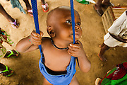 A child sits in the harness of a scale outside the Kaniya PHU in the village of Kaniya, Sierra Leone, on Friday April 23, 2010..