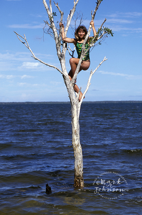 Australia, Queensland, Lake Cootharaba, 11 y.o. girl climbing tree in lake people ****Model Release available
