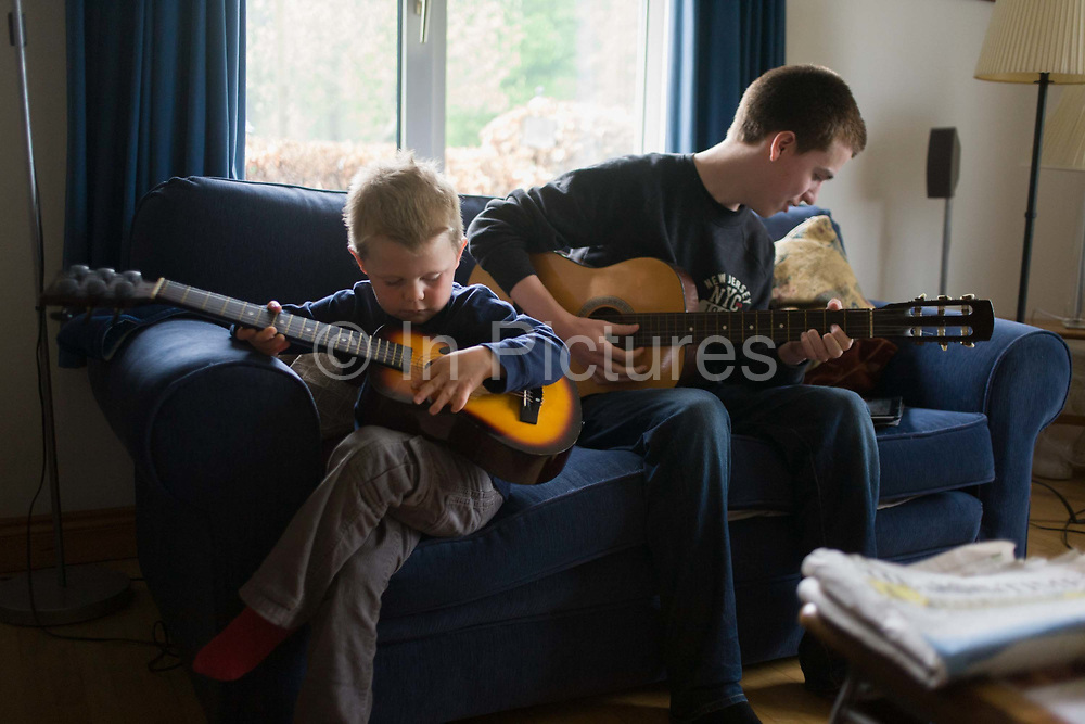 A 16 year-old teenager and his 4 year-old cousin sit on a sofa to play acoustic guitar together in the family living room. Playing their musical instruments, the older boy knows how to pluck the strings to make a pleasant sound while the younger lad simply brushes his fingers across the strings to make a noise. But music brings their age gap closer as they perform a pretend concert in front of family elders.