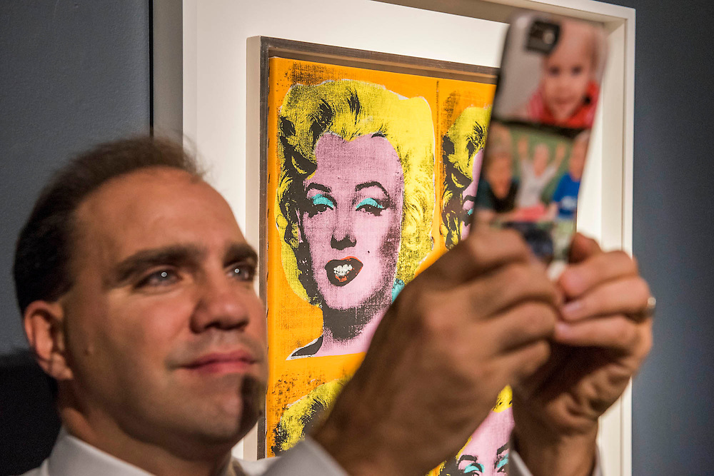 A staff member takes a selfie in front of Four Marilyns by ANDY WARHOL (1928-1987)<br /> Painted in 1962.<br /> Estimate on Request - Christie's showcases  the London Post-War and Contemporary Art Evening Sale in October, alongside an exceptional selection of works from the  New York sales in November of Impressionist, Modern, Post-War And  Contemporary Art. The works will be on view to the public from Saturday 10 October to Saturday 17 October at Christie's King Street. The highlight is  Amedeo Modigliani's, 'Nu couché (Reclining  Nude)', painted in 1917-18, which has an estimate in the region of $100 million.