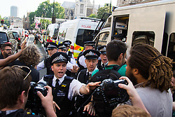 London, June 21st 2017. Protesters march through London from Sheherd's Bush Green in what the organisers call 'A Day Of Rage' in the wake of the Grenfell Tower fire disaster. The march is organised by the Movement for Justice By Any Means Necessary and coincides with the Queen's Speech at Parliament, the destination. PICTURED: Police stop protesters approaching a van containing an arrested protester.